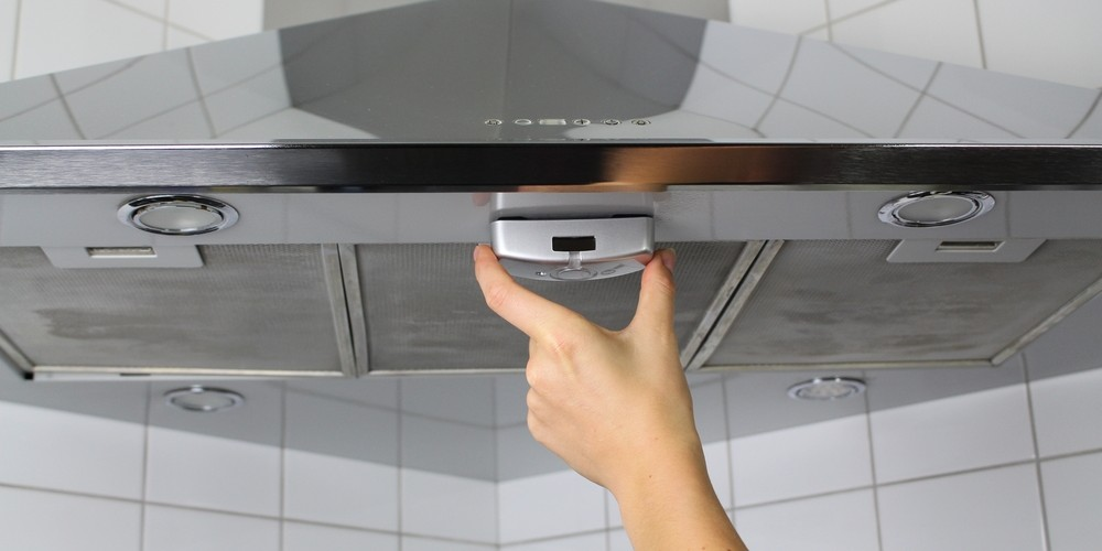 Dies Bild zeigt die einfache Installation des Produktes Gorilla®-stove: unter die Dunstabzugshaube klipsen, Magnete halten es dort fest, 5 Jahre Garantie, 15 Jahre kein Batteriewechsel. (Quelle: obs/Gorilla Electronics GmbH)